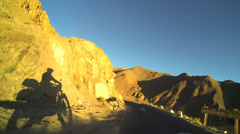 POV rider in motion silhouetted at sunset, Khardung Pass, Ladakh, India          - stock footage