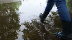 Woman in waterproof boots shoes walk puddle water in rain Stock Footage