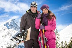 couple with skis in snow - stock photo