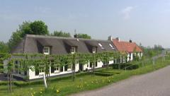 Ooijpolder river dike with roadside flora + pan workers cottages + cyclists Stock Footage