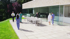 Diverse medical team walking outside modern health care facility - stock footage