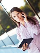 young businesswoman with cellphone and organizer while standing against offic - stock photo