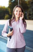 Young businesswoman with cellphone and organizer while standing against offic Stock Photos