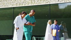 Caring medical worker helps a patient to walk on crutches Stock Footage