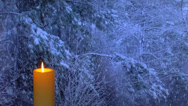 Stock Video Footage of Golden candle glows with snow falling outside in the background