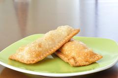 Crispy pies in green plate on wooden table. Stock Photos