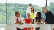 Stock Video Footage of Business team meeting in light contemporary office with natural outdoor views