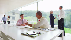 Two young businessmen in discussion in contemporary glass office Stock Footage