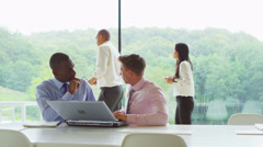 Two businessmen in discussion in contemporary glass office Stock Footage