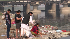 A girl is performing a Hindu ritual at the bank of Yamuna River Stock Footage