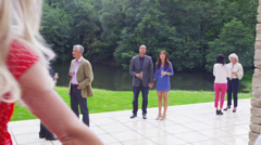 Young couple holding hands and guests chatting at outdoor drinks party Stock Footage