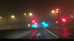 Car moving the dense early morning fog blinking traffic light Stock Footage
