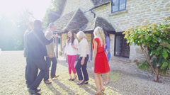 Cheerful host and hostess welcome guests to their home for a social gathering - stock footage
