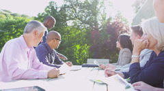 Business group in outdoor meeting in natural setting on a sunny day Stock Footage