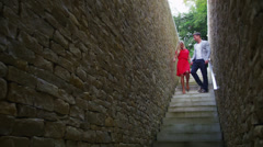 Attractive young couple walking down a set of stone stairs pause to share a kiss Stock Footage