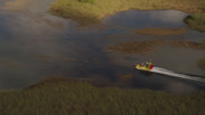 Stock Video Footage of Wide aerial shot tracking a fanboat racing through marshland in the Everglades