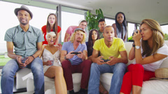 Happy group of friends socializing at home and playing video games Stock Footage