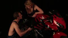 Flirtation between mechanic and motorcyclist Stock Footage