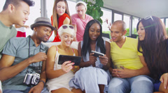 Happy group of friends socializing at home and having fun with their technology - stock footage