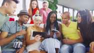 Happy group of friends socializing at home and having fun with their technology Stock Footage
