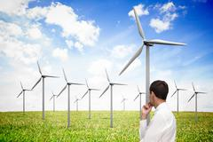 Thoughtful classy businessman looking at windmill Stock Photos