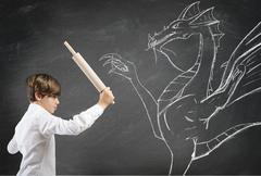 brave boy fighting a dragon - stock photo