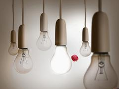 Red apple being thrown between light bulbs - stock illustration