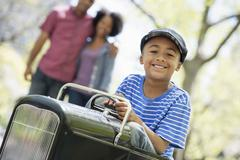 A boy riding an old fashioned peddle car Stock Photos