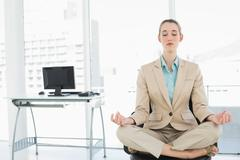 Concentrated calm businesswoman sitting in lotus position on her swivel chair - stock photo