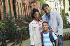 A family on a street, two adults and boy - stock photo