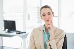 Thoughtful calm businesswoman sitting on her swivel chair - stock photo