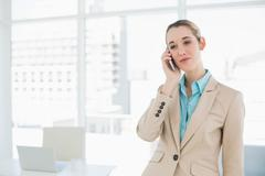 Concentrated classy businesswoman phoning with her smartphone - stock photo