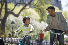 A father and son cycling in a park Stock Photos