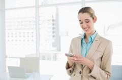 Content classy businesswoman texting with her smartphone Stock Photos