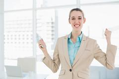 Attractive cheerful businesswoman holding her smartphone - stock photo