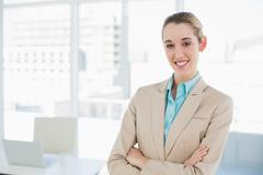 Lovely smiling chic businesswoman posing with arms crossed smiling at camera Stock Photos