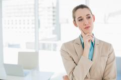 Cute thoughtful chic businesswoman standing in her office Stock Photos