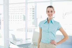 Cheerful attractive businesswoman posing with hand on hip - stock photo