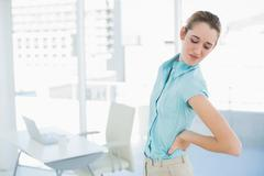 Gorgeous suffering businesswoman holding her injured back - stock photo
