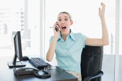 Extremely happy chic businesswoman phoning while cheering - stock photo