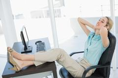 Classy young businesswoman relaxing sitting on her swivel chair - stock photo