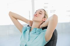 Beautiful peaceful businesswoman relaxing on her swivel chair Stock Photos