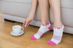 Young slender woman wearing pink socks sitting on couch - stock photo