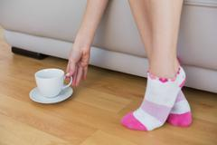 Slender woman wearing pink socks reaching for a cup - stock photo