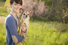 A woman with a small pet Chihuahua dog - stock photo