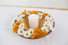 Flate full of flowers and a lit candle - stock photo