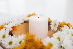 Flowers and a lit candle Stock Photos