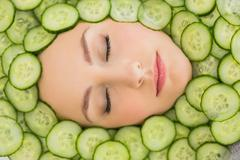 Beautiful woman with facial mask of cucumber slices on face - stock photo