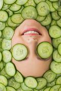 Stock Photo of Beautiful woman with facial mask of cucumber slices on face