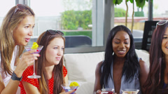 Happy female friends drinking cocktails and chatting together Stock Footage